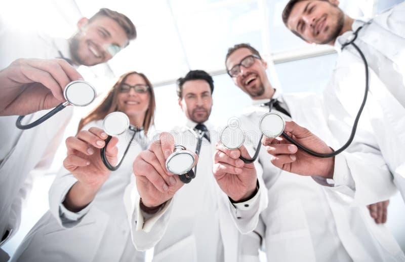 Vista dal basso un gruppo di medici ha un i loro stetoscopi immagini stock libere da diritti