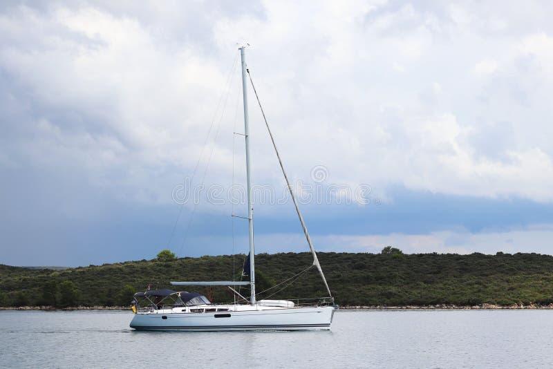 Vista dal lato all'yacht di navigazione che va sotto il motore dopo la riva verde contro il cielo con le nuvole di tempesta Resto fotografia stock libera da diritti