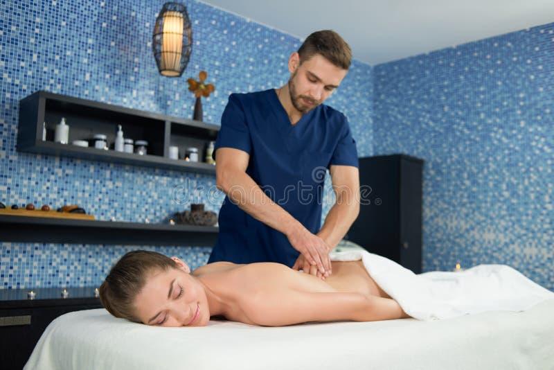 Vista dal lato della donna che riceve massaggio di rilassamento in stazione termale fotografia stock