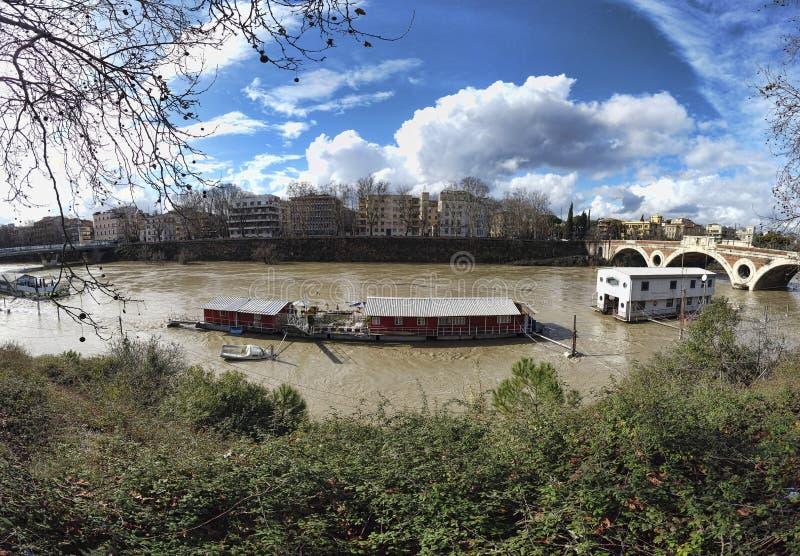 Vista dal Lungotevere verso il fiume con le barche del club di De Pinedo River e le caserme di galleggiamento del fuoco fluviale  fotografia stock libera da diritti