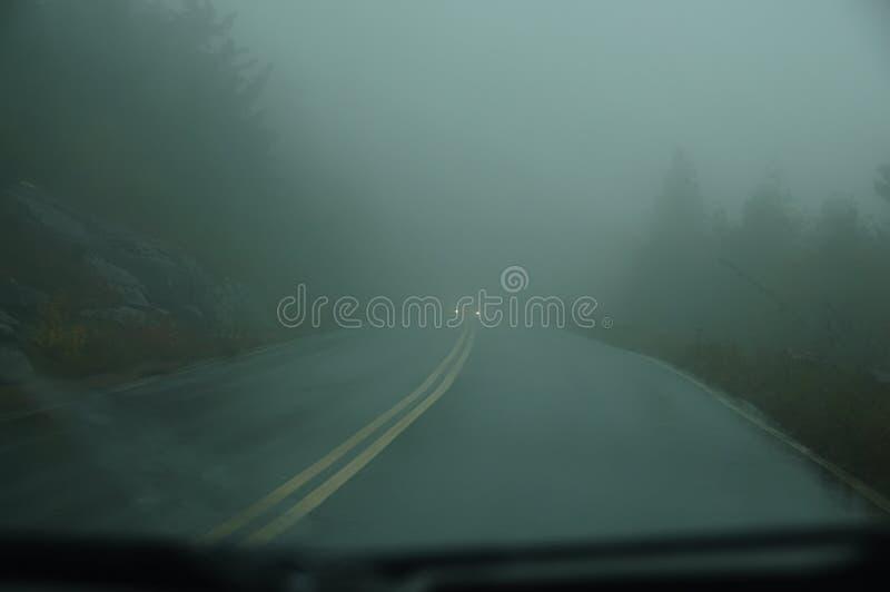 Vista dal parabrezza dell'automobile sulla strada in una forte foschia e nei fari di un'automobile imminente La strada è nel da s fotografia stock