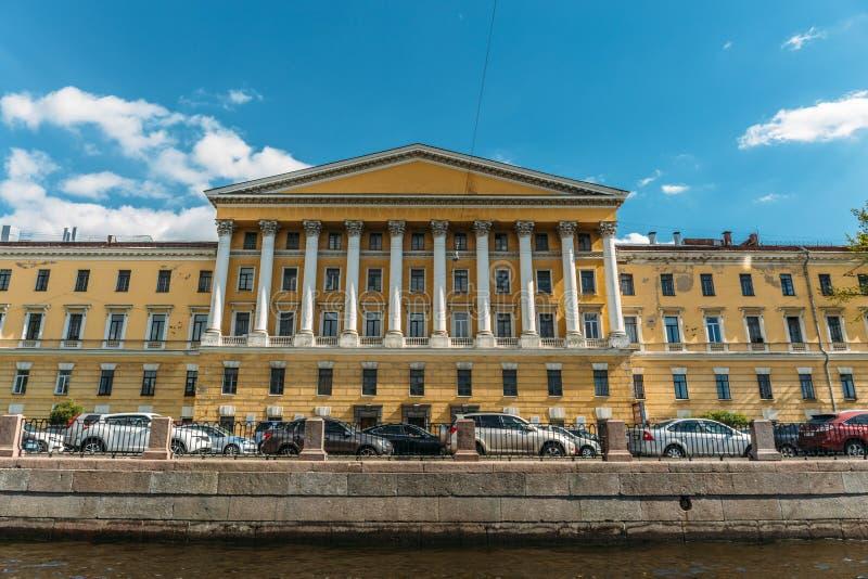 Vista dall'acqua ad una bella costruzione gialla con le colonne sull'argine di St Petersburg, Russia fotografia stock