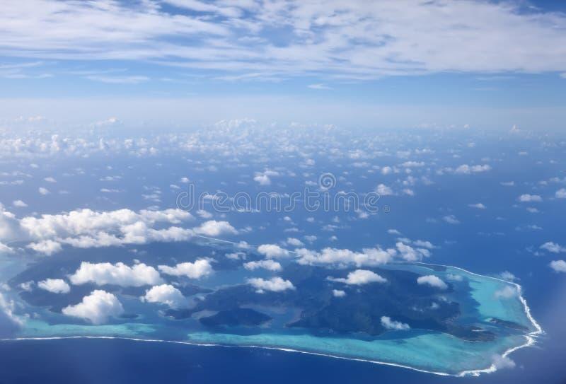 Vista dall'aereo alle isole coralline nel mare sotto le nuvole, Polinesia, Tahiti fotografie stock