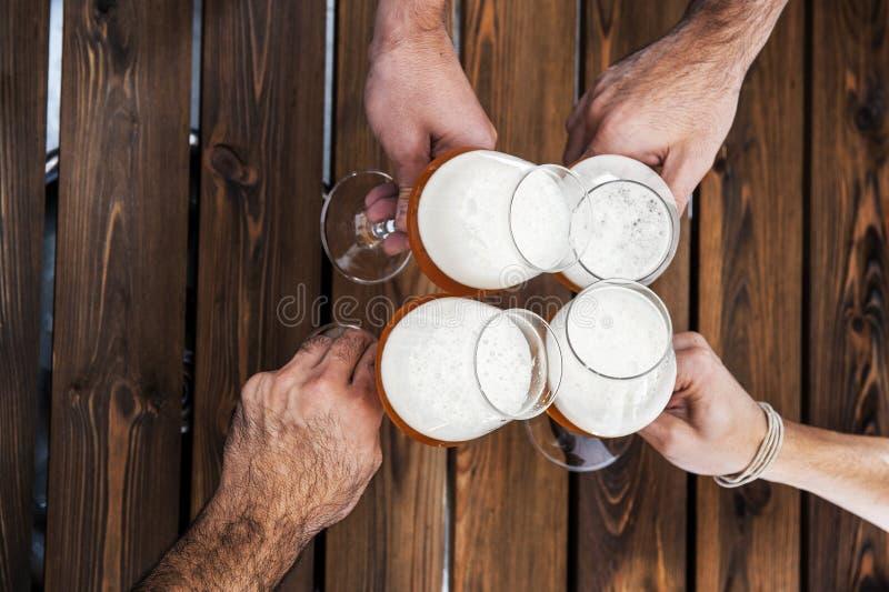 Vista dall'alto di quattro mani con birre che applaudono e si divertono insieme immagini stock libere da diritti
