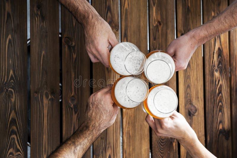 Vista dall'alto di quattro mani con birre che applaudono e si divertono insieme immagine stock