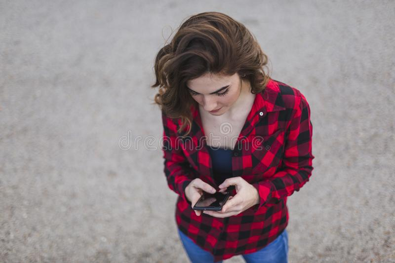 vista dall'alto di un ritratto di una giovane bellissima donna che usa il cellulare Lei sta indossando dei vestiti casuali Estern immagine stock