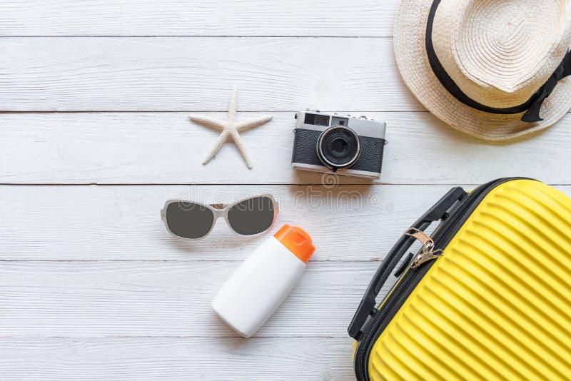 Vista dall'alto Viaggi e piani estivi Bagagli in valigia gialla con accessori moda, vecchia telecamera, blocco solare su fondo bi immagini stock