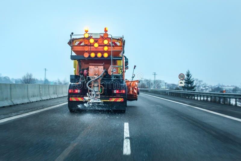 Vista dall'automobile dietro il camion arancio di manutenzione della strada principale fotografia stock libera da diritti