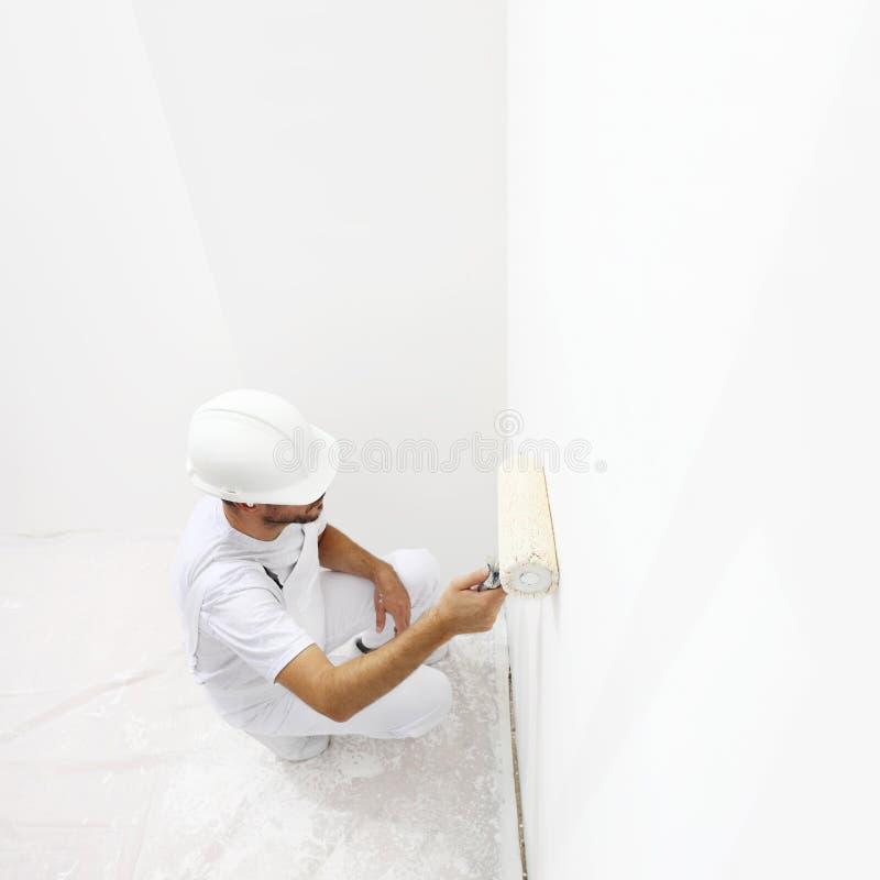 Vista dall'uomo superiore del pittore sul lavoro con un rullo di pittura, dolore della parete fotografia stock libera da diritti