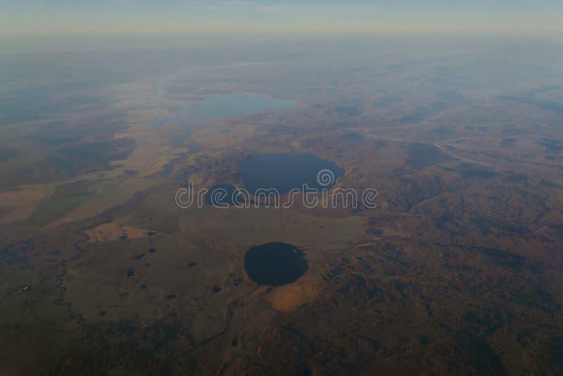 vista dalla finestra dell'aereo all'orizzonte del lago e del fiume nelle montagne con le foreste al tramonto del giorno immagini stock