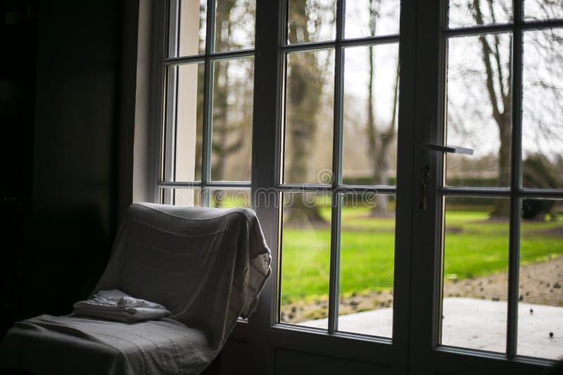 Vista dalla finestra sulla mattina nuvolosa del giardino verde fotografia stock libera da diritti