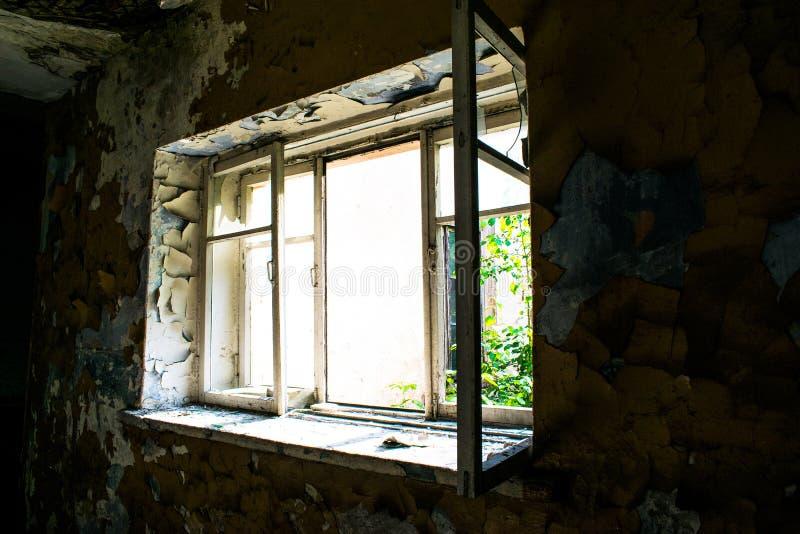 Vista dalla finestra in una vecchia casa abbandonata fotografia stock
