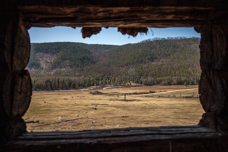 Vista dalla grande finestra al campo con un'azienda agricola e un fiume fotografia stock