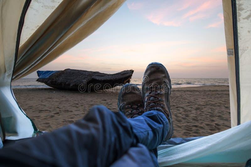 Vista das barracas em um Sandy Beach pelo mar e em um barco no por do sol Viagens e expedições no selvagem Conceito do acampament imagens de stock royalty free