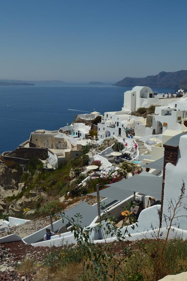 Vista das casas com o telhado arcado azul com vista do Mar Egeu azulado na ilha de Santorini da cidade de Oia Arquitetura, paisag imagens de stock