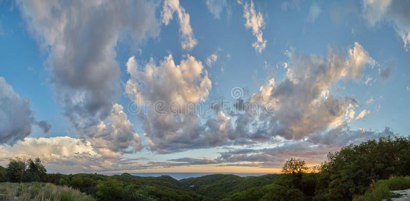 Vista das colinas verdes perto do mar e lindas nuvens cumulus no pôr do sol foto de stock