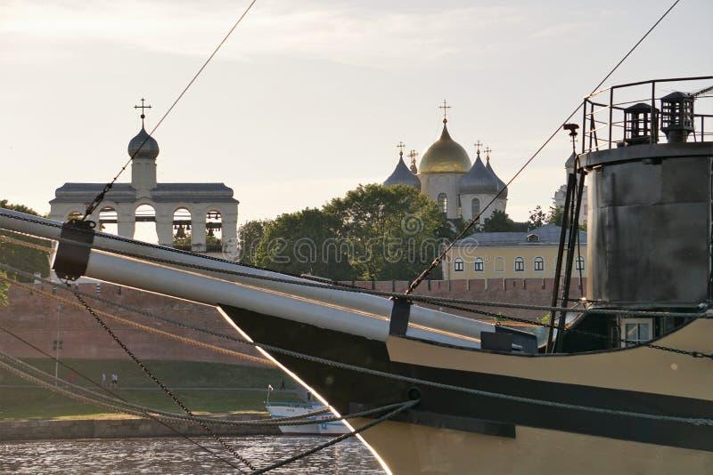 Vista das construções históricas no Kremlin de Novgorod através dos gurupés do navio-restaurante no rio de Volkhov imagem de stock royalty free