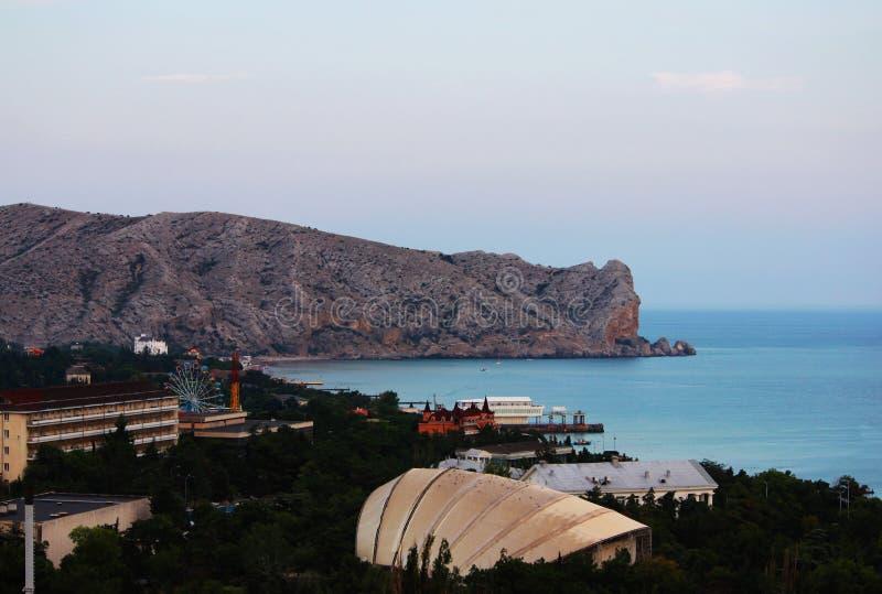 A vista das montanhas e do Mar Negro após o por do sol sobre as montanhas Paisagem da noite e cidade Sudak, a república do CRI fotos de stock royalty free