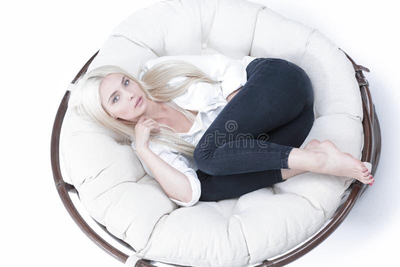 Vista de acima Close-up de uma jovem mulher triste bonita que encontra-se em uma grande cadeira confortável imagens de stock royalty free
