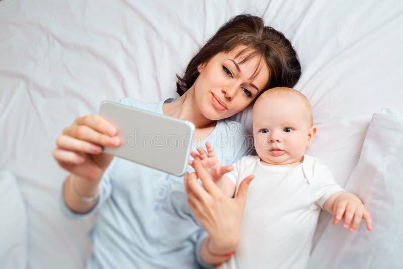 Vista de acima Selfie Mamãe e a criança com o telefone no b imagens de stock royalty free