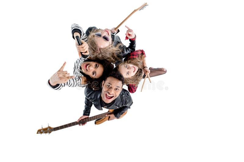 Vista de arriba de la banda de rock-and-roll joven feliz que presenta con los instrumentos fotos de archivo