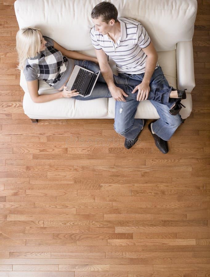 Vista de arriba de los pares que se relajan en el sofá foto de archivo libre de regalías