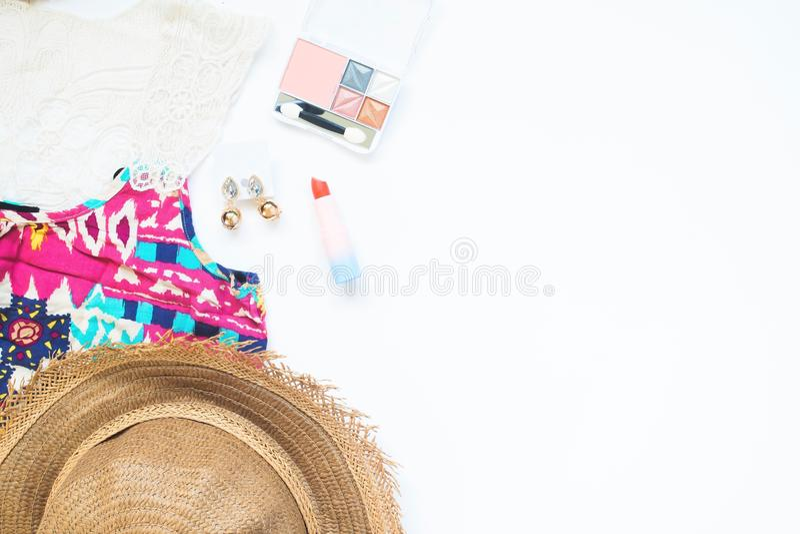 Vista de arriba del esencial y de los cosméticos de la mujer en el fondo, la playa y la moda blancos de la belleza imagenes de archivo