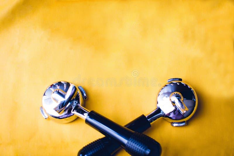 Vista de arriba del tenedor del filtro de la m?quina del caf?, granos de caf?, barra del chocolate, cafetera en fondo amarillo fotografía de archivo