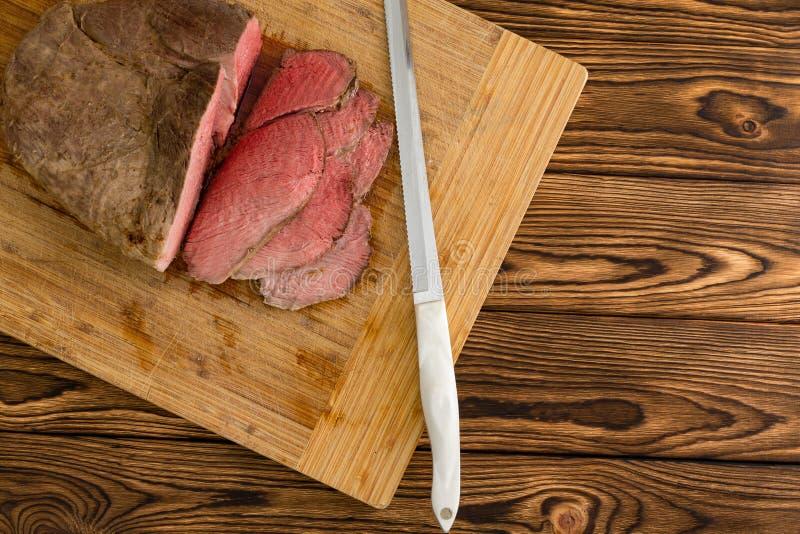 Vista de arriba de la carne cortada al lado del cuchillo imágenes de archivo libres de regalías