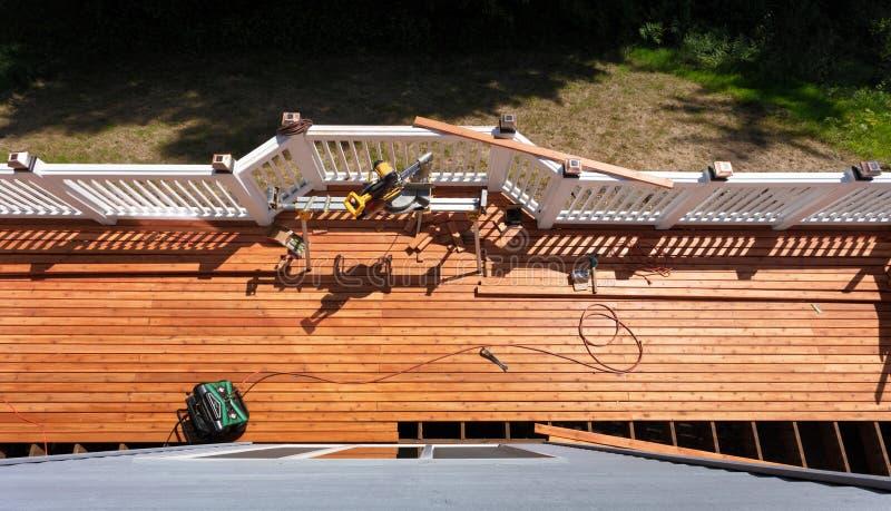 Vista de arriba de la cubierta de madera del cedro al aire libre que es remodelada con las herramientas del poder y de la mano en fotos de archivo libres de regalías
