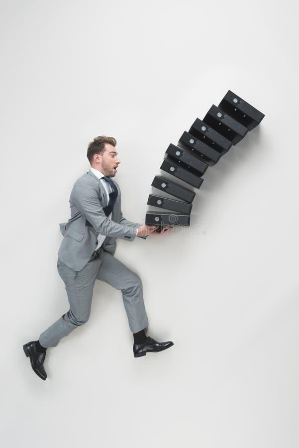 vista de arriba de la pila que lleva del hombre de negocios joven de carpetas que caen foto de archivo