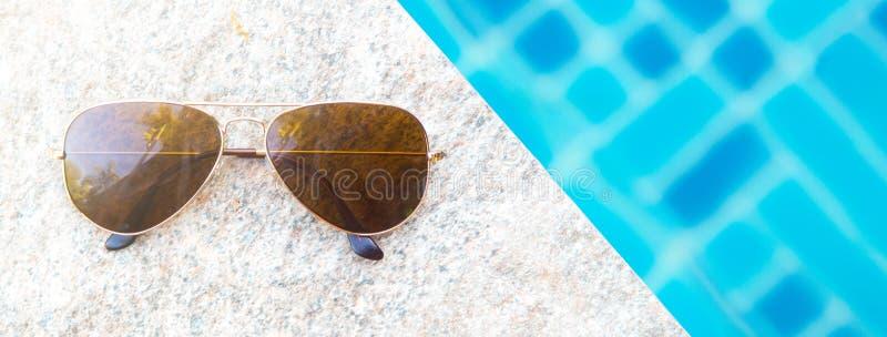 Vista de arriba de las gafas de sol y del poolside de la moda Concepto de las vacaciones de verano Tamaño de la bandera con el es imagenes de archivo