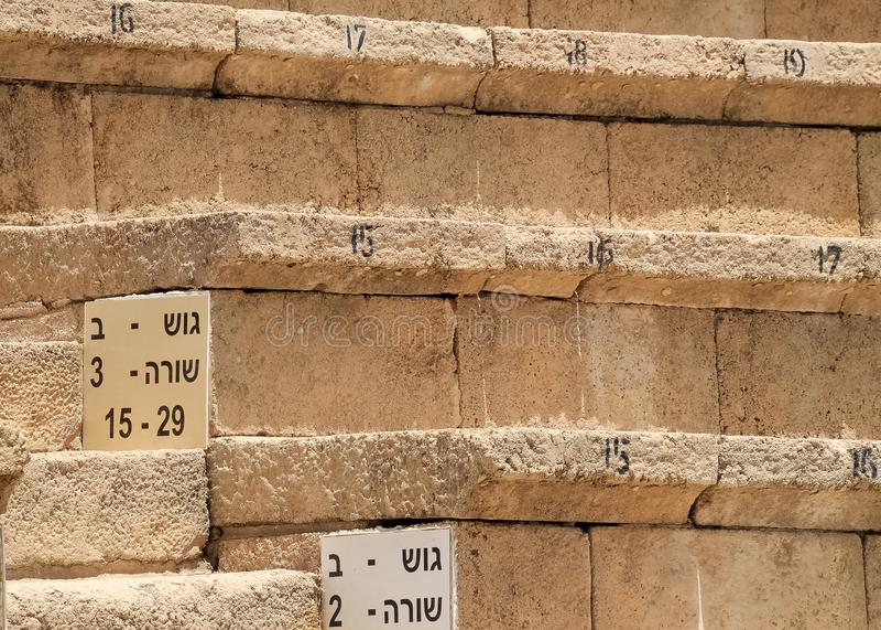 Vista de asientos numerados en el teatro de Caesarea en la costa mediterr?nea foto de archivo