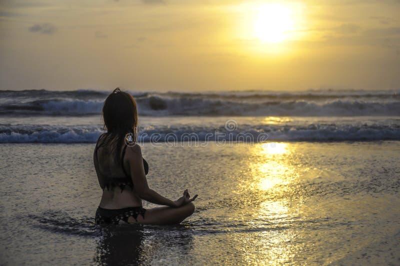 Vista de assento da mulher livre à ioga praticando do por do sol do mar e meditação na praia asiática bonita fotografia de stock