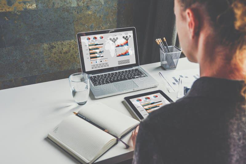 Vista de atrás, mulher de negócios que sentam-se na mesa e trabalho Estudante que aprende em linha Planeamento empresarial fotografia de stock royalty free