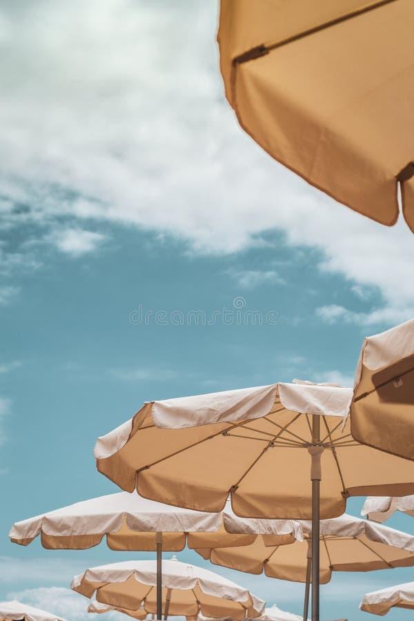 Vista de baixo dos céus azuis em uma praia com os parasóis sobre cadeiras de plataforma imagem de stock royalty free