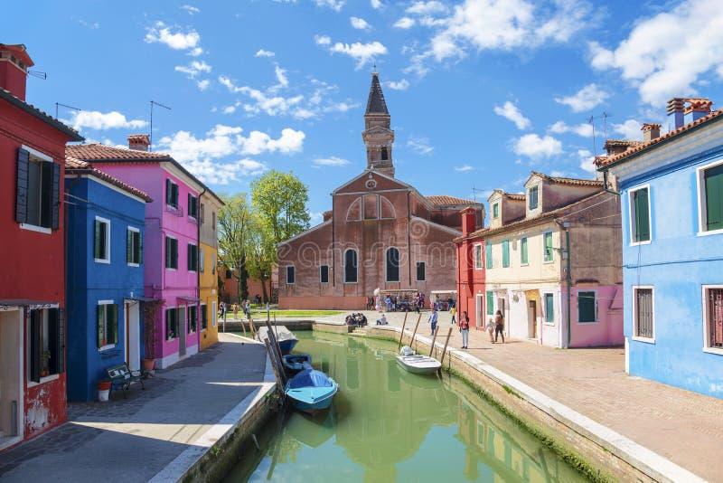 Vista de Burano com casas coloridas e a igreja de San Martino com uma torre de sino de queda Veneza imagem de stock