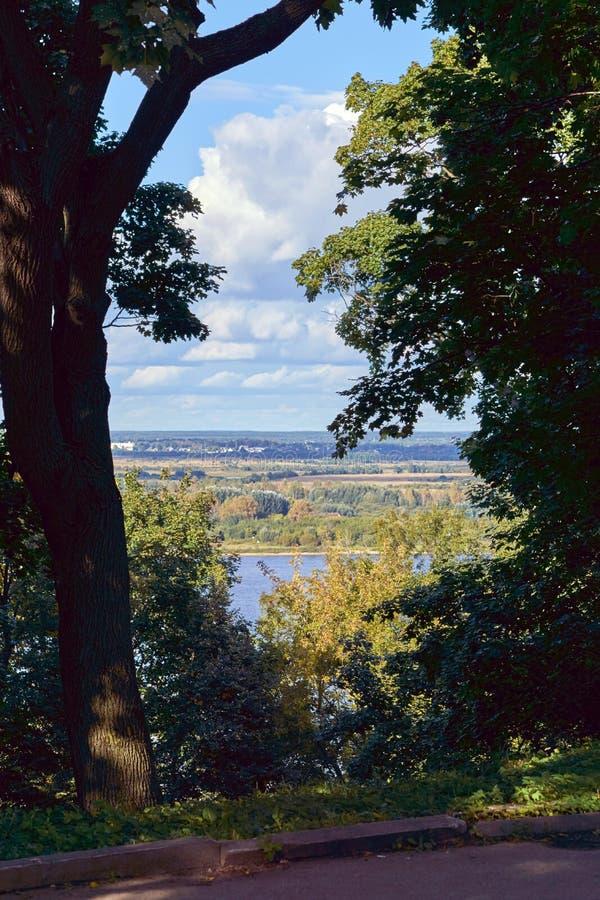 Vista de campos, de bosques y de prados en el otro lado de un río o de una charca grande del alto banco fotos de archivo