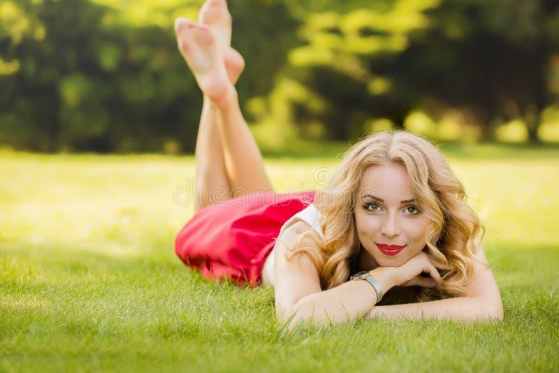 Vista de cima da atraente modelo feminino deitada na grama verde no parque e olhando para a câmera durante o tempo de repouso, re fotografia de stock royalty free