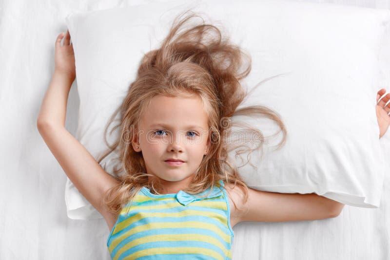 A vista de cima da criança fêmea bonita pequena bonita com cabelo leve, vestido em pyjamass listrados, encontra-se no descanso, t fotos de stock
