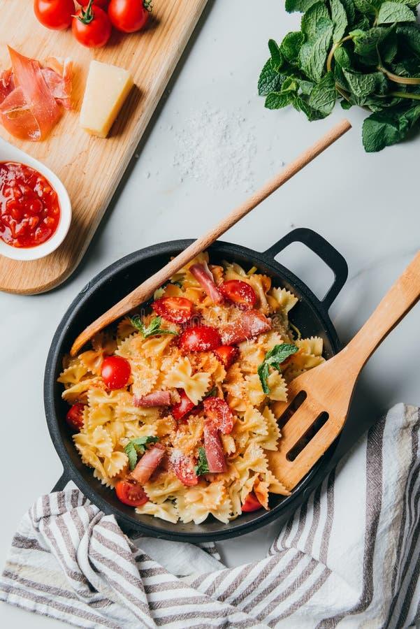 vista de cima da massa com jamon, tomates de cereja, folhas de hortelã cobertas pelo Parmesão raspado na bandeja com a espátula d imagens de stock