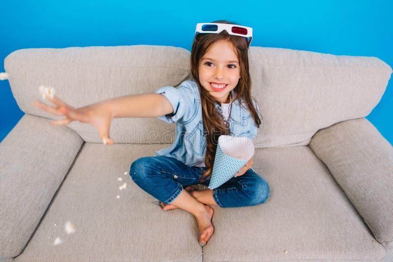 Vista de cima da menina alegre com cabelo moreno longo na roupa das calças de brim que sorri no sofá no fundo azul fotos de stock