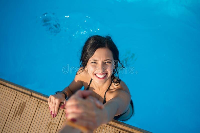 Vista de cima da menina na piscina que guarda uma mão do ` s do homem que tenta sair no dia ensolarado fotografia de stock