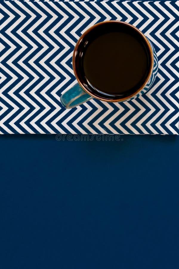 Vista de cima da xícara de café preto no guardanapo têxtil sobre fundo azul com espaço para cópia fotos de stock royalty free