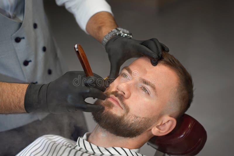 Vista de cima do homem na cadeira quando barbeiro que barbeia a barba foto de stock royalty free