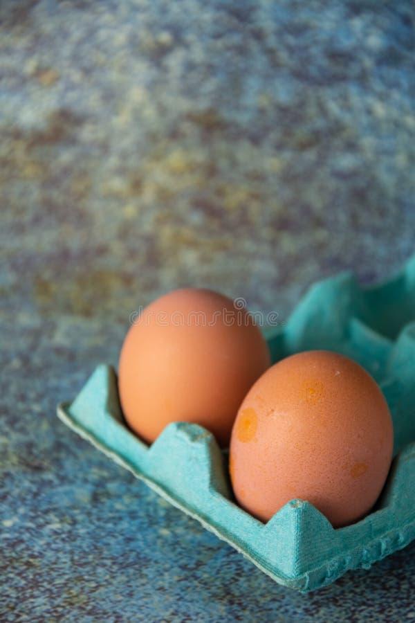 Vista de cima de dois ovos marrons em caixa de papelão verde, com foco seletivo, em fundo desgastado e azulado, na vertical fotos de stock royalty free