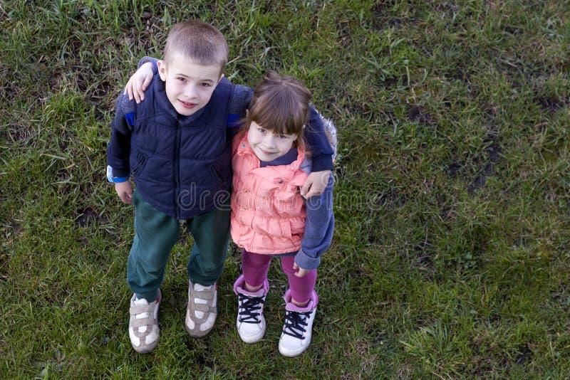 Vista de cima de duas crianças bonitos na roupa ocasional menino e menina que estão na grama verde, abraçando-se sobre ombros, lo fotos de stock royalty free
