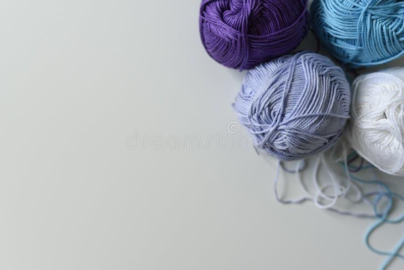 Vista de cima nas bolas coloridas do fio para tricotar manualmente, no fundo branco da tabela fotografia de stock