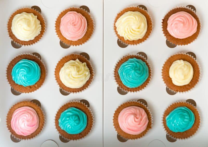 A vista de cima no azul, do rosa e do branco cozeu recentemente queques imagens de stock royalty free