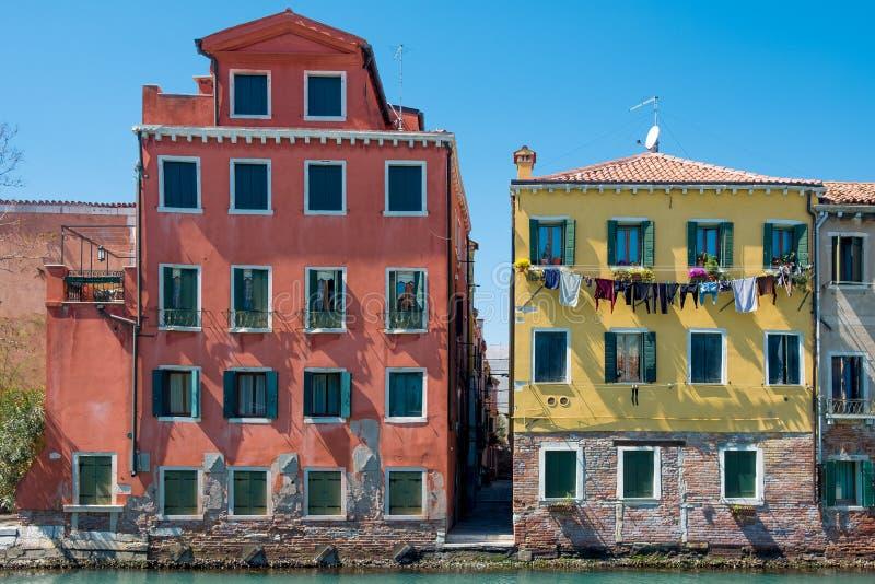 Vista de construções venetian coloridas em vermelho e em amarelo com canal da água e o céu azul claro durante o dia de verão enso fotos de stock